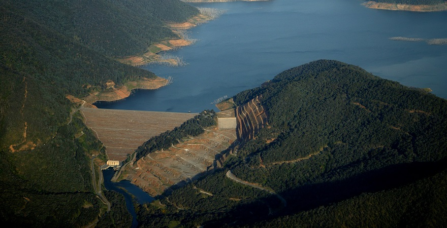 Aerial view of Dartmouth Dam, with the water behind the dam wall visible surrounded by bushland.