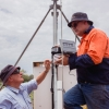 two men looking at a device on a pole at a flat rural property.